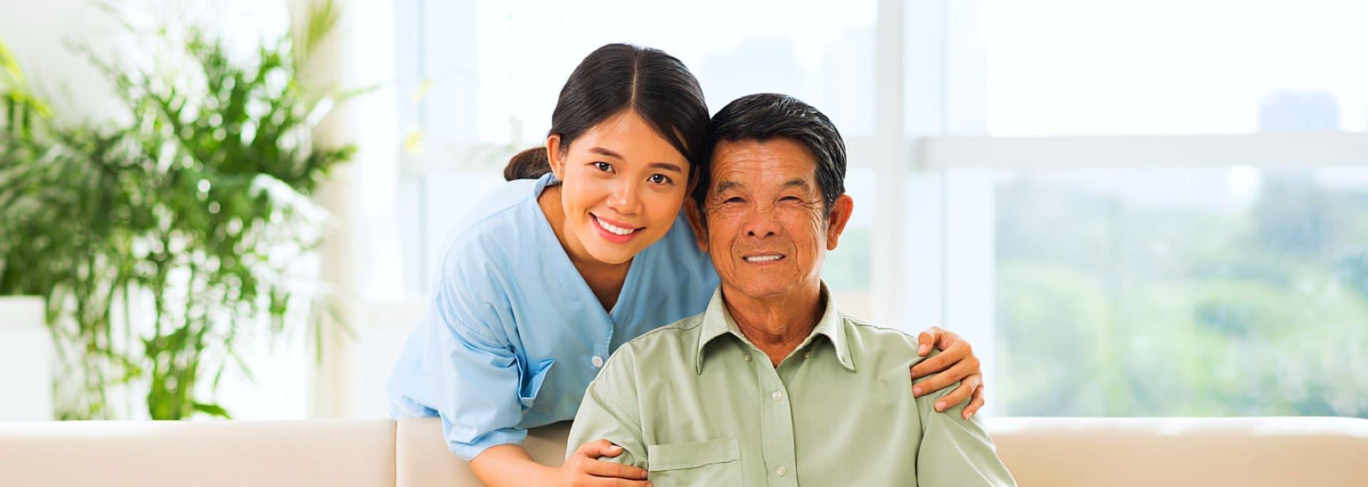 caregiver hugging senior man at the back