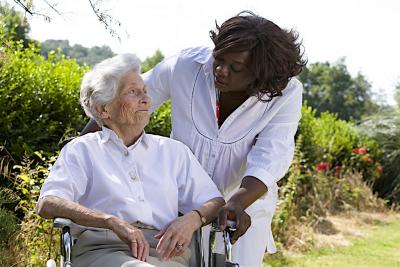 caregiver talking to disabled senior woman