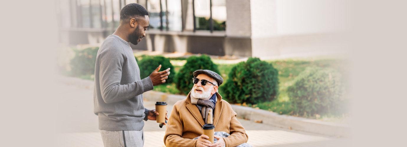senior man and caregiver drinking coffee